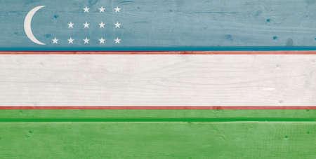 Uzbekistan flag painted on wood plank background. Brushed natural light knotted wooden board texture. Wooden texture background flag of Uzbekistan