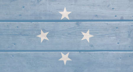 Micronesia flag painted on wood plank background. Brushed natural light knotted wooden board texture. Wooden texture background flag of Micronesia