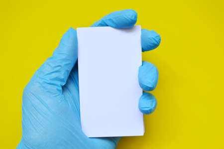 A hand in a blue rubber glove holds a white blank paper on a yellow background.