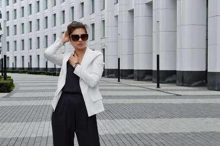 Beautiful business woman on the background of the modern office. Girl in black overalls and sunglasses posing near the business center 免版税图像