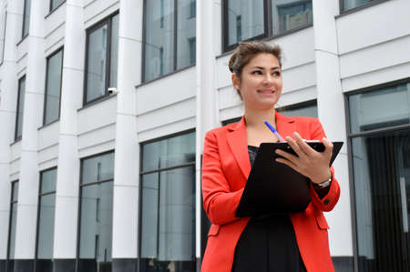 Beautiful business woman on the background of the modern office. Girl in black overalls and red jacket with a tablet in her hands near the business center Imagens