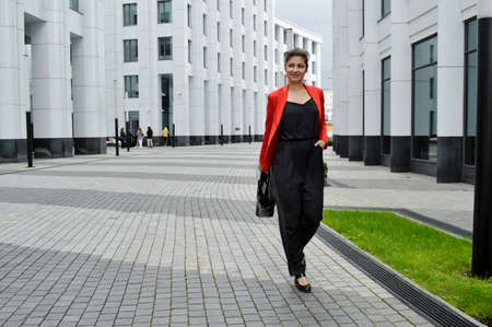 Beautiful business woman on the background of the modern office. A girl in a black overalls and a red jacket is walking near the business center