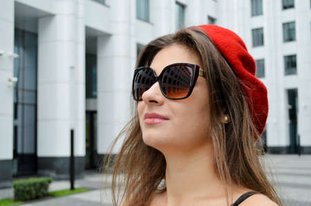 Beautiful business woman on the background of the modern office. Portrait of a girl with dark hair in a black top on thin spaghetti straps, sunglasses and a red beret near the business center