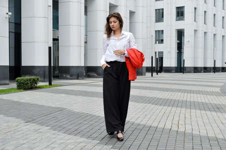 Beautiful business woman on the background of the modern office. The girl with dark hair in a white shirt and black trousers with a red jacket in his hands near the business center