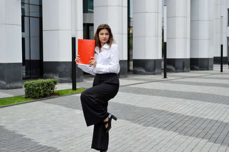 Beautiful business woman on the background of the modern office. The girl with dark hair in a white shirt and black trousers with a red folder in hands is happy near the business center