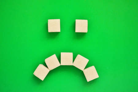 Sad emoticon from refined sugar on a green background