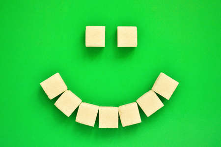 Cheerful emoticon from refined sugar on a green background