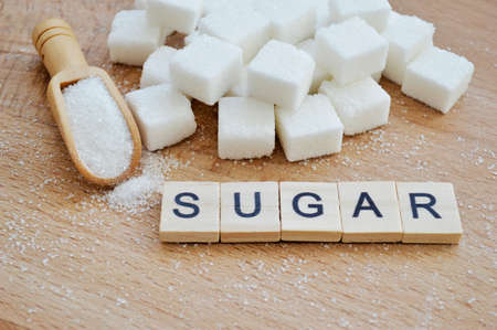 Refined sugar and wooden spoon with loose sugar on wooden background. Word sugar of wooden blocks with letters