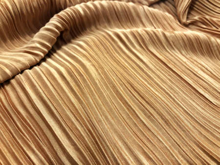 Gold texture of crumpled fabric with drapery