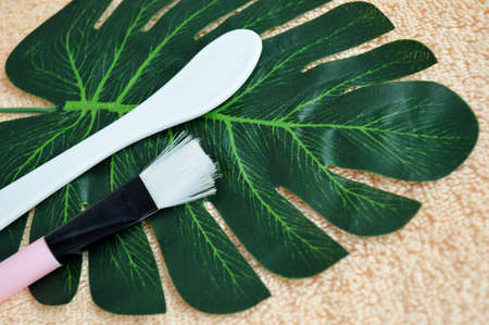 Shovel and brush for applying the mask lie on palm leaf on a background of beige fabric