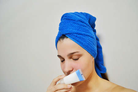 Woman with a towel on his head on a light background is holding a cream in a tube