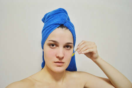 Woman with a towel on her head on a light background applies oil to her face through a pipette