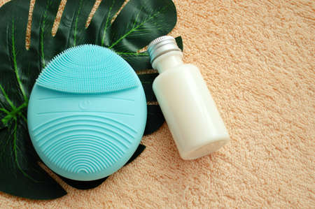 Facial brush and plastic bottle lie on palm leaf on beige cloth background Stock Photo