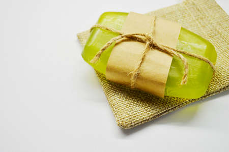 Green soap tied with rope and brown paper lies on a white background on a jute bag