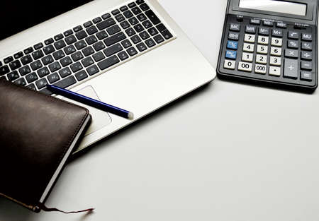 Accountant's Day. Calculator, notebook, pen and old notepad on white background.
