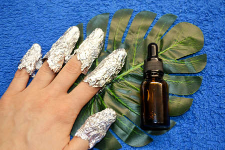 Removing shellac from nails. fingers with foil and glass bottle with a pipette on a green leaf of a palm tree on a blue background. Close-up hand. Front view. Imagens