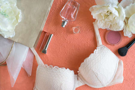 Light pink bra and make up products on the peach color background.