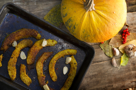 Roasted pumpkin on a baking tray on rustic wooden table photo