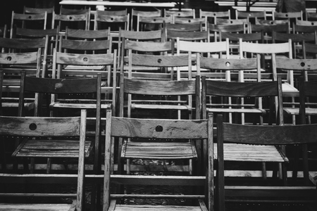 dozens: Black and white picture made on Jazz Festival depicting many wooden chairs standing under rain covered with dozens of raindrops.