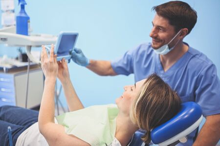Dentist shows patient the results of treatment with a mirror, examinating teeth with dental equipment in dental office. Young handsome male doctor in medical facial mask and smiling happy woman.