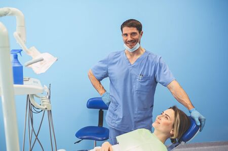 Dentist examining a patients teeth using dental equipment in dentistry office. Stomatology and health concept. Young handsome male doctor in disposable medical facial mask, smiling happy woman.