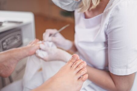 Professional medical pedicure procedure close up using double nail instrument. Patient visiting chiropodist podiatrist. Foot treatment in SPA salon. Podiatry clinic. Pedicurist hands in white gloves