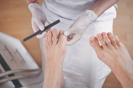 Pedicurist doing professional medical pedicure procedure in beauty salon with nail file. Foot treatment in SPA salon. Podiatry clinic. Beautician doctor hands in white gloves with female legs