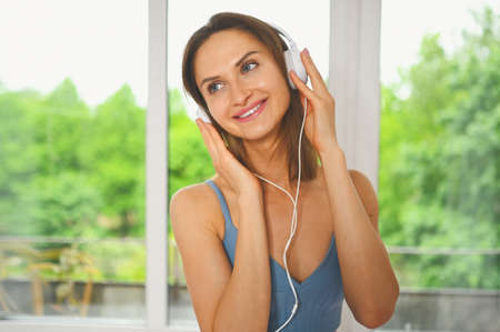 Young happy smiling beautiful slim fit girl in blue sportswear is listening to music in big white headphones at home against the window. Girl with perfect body getting ready for yoga or exercises
