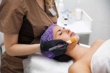 Young woman cleaning face skin in beauty salon.Facial brush peel retinol treatment. Beauty woman peeling procedure. Cosmetology young girl therapy. Hyaluronic acid. Aesthetic Cosmetology concept  Standard-Bild