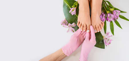 Beautiful perfect female skin legs feet top view with tropical flowers and green palm leaf. Nail polish, care and clean, spa pedicure treatment in white. Concept on a white background. Copy space