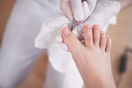 Professional medical pedicure procedure close up using nail clippers instrument. Patient visiting chiropodist podiatrist. Foot treatment in SPA salon. Podiatry clinic. Pedicurist hands in white gloves
