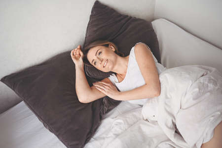 Attractive smiling young woman stretching in bed waking up alone, awake after healthy sleep in cozy comfortable bed and mattress enjoy good morning