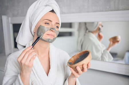 Beautiful smiling woman at home in bathrobe with a towel applying face clay mask against acne to rejuvenate problem skin