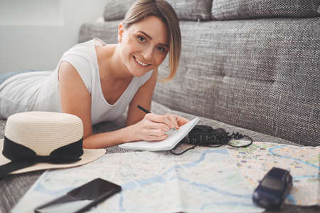 Happy woman planning vacation travel trip at home after end of pandemic and quarantine. Girl looking at a map writes information to a notebook.