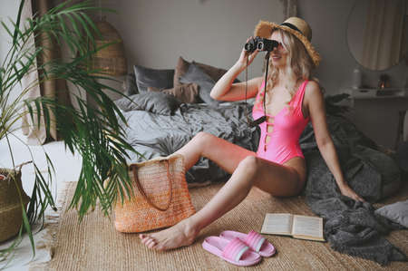 Sexy blonde woman in pink swimsuit imitating summer beach vacation time at home bedroom interior. Coronavirus situation in tourism travel industry. Fun quarantine. Stay at home, Isolation.