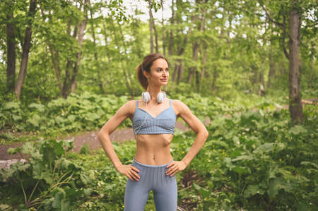 Young happy beautiful slim fit girl in blue sportswear with big white headphones doing squats exercise with fitness training gum in the summer green park outdoor. Girl with perfect body, sport yoga