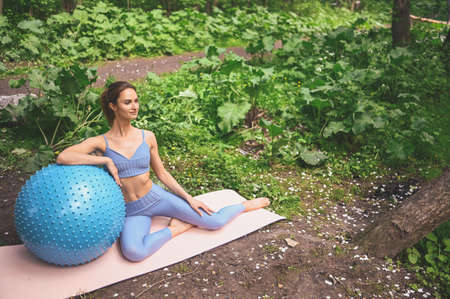 Young beautiful slim fit girl in blue sportswear with big white headphones doing squats exercise with fitness training gum in the summer green park outdoor with pink yoga mat. Girl with perfect body