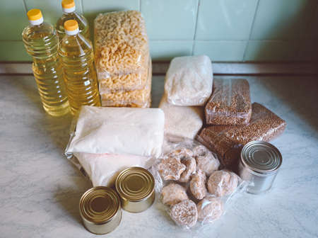 Volunteer donation various product set for poor or elderly people. Pandemic coronavirus food shortages. Food donations or delivery concept on kitchen background.