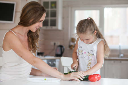 Happy family mother and child posing at home. Beautiful young mom and little daughter having fun and preparing vegetables for salad in a white kitchen in a Scandinavian style interior. Healthy food Archivio Fotografico
