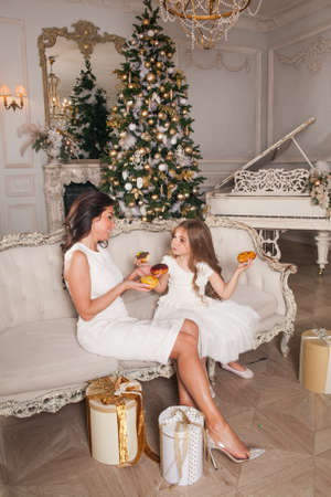 Little happy cute girl with beautiful young mother having fun and eating donuts against the background of a decorated Christmas tree in classic interior. Happy family in the New Year festive night.