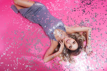 Amazing excited beautiful blonde in silver sparkle dress smiling lady draws attention to great cool event, concert, sale, discount message, isolated pink background with confetti. Free space for text Stock fotó