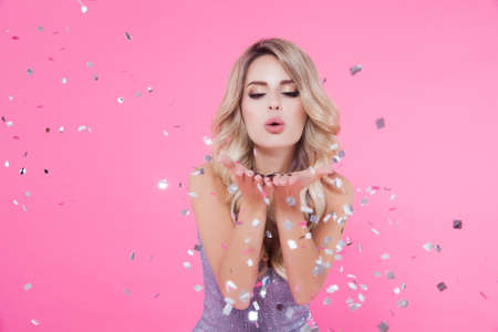 Woman celebrating New Year, Happy Birthday, cool event party. Portrait of beautiful excited smiling girl in shiny silver dress throwing confetti on pink background. Copy space for text mockup Stock fotó