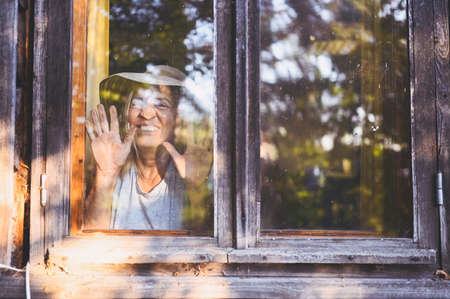 Happy smiling emotional elderly woman having fun posing by open window in rustic old wooden village house in straw hat. Retired old age people concept. Quarantine in the country house