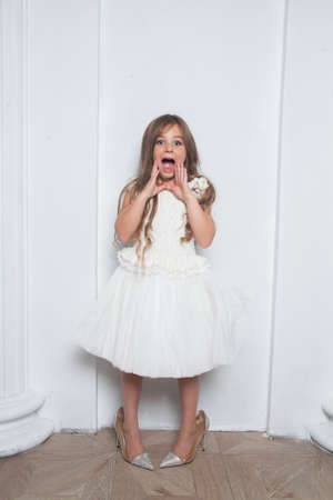 Little princess - excited emotional cute girl in fashion white dress having fun and wearing big mothers sparkle high heels shoes on white background. Free space for text mockup