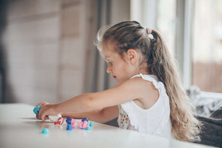 Little cute preschooler child girl playing educational games with plasticine figures preparing for school in kindergarten while sitting at table. Back to school concept