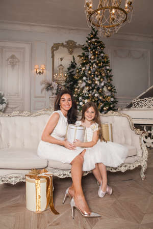 Merry Christmas and Happy Holidays. Cheerful mom and her cute daughter girl exchanging gifts in white classic interior against the background of a piano and a decorated Christmas tree. New Year 2021