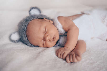 Cute emotional newborn little baby boy sleeping in crib in a knitted suit with ears. Baby goods packaging template. Healthy child, concept of hospital and happy motherhood. Infant baby. Nursery.