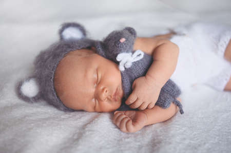 Cute emotional newborn little baby boy sleeping in crib in a knitted suit with toy. Baby goods packaging template. Healthy child, concept of hospital and happy motherhood. Infant baby. Nursery.
