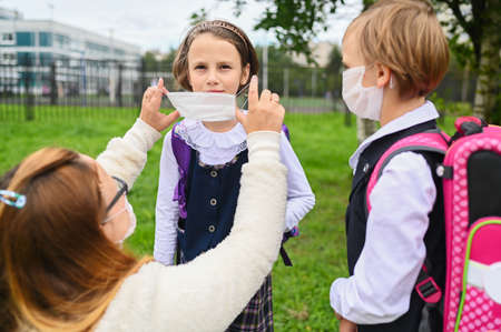 Mother puts a safety mask on her daughter's face. Schoolgirls ready go to school. Little sisters with a backpack outdoors. Back to school. Medical mask to prevent coronavirus. Social distance