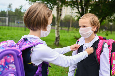 Little cute girls with safety protection mask on faces. Schoolgirls ready go to school. Little sisters with a backpack outdoors. Back to school. Medical mask to prevent coronavirus. Social distance